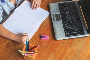 Junge macht Hausaufgaben mit Notizbuch, Laptop, Hefter und einer Tasse Bleistifte auf einem Holzschreibtisch foto