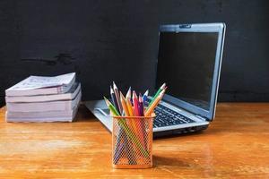 Tasse Bleistifte, ein Laptop und ein Stapel Bücher auf einem Holztisch neben einer schwarzen Wand