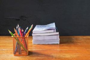 Tasse Bleistifte und ein Stapel Bücher auf einem Holztisch neben einer schwarzen Wand