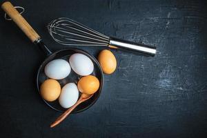 rohe Eier in einer Pfanne mit Holzlöffel und Schneebesen auf einem Holztischhintergrund