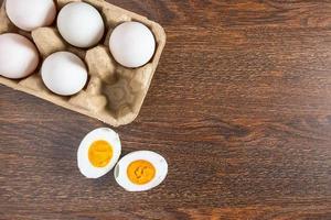 halbiertes hart gekochtes Entenei neben ganzen Eiern in einem Karton auf einem Holztisch