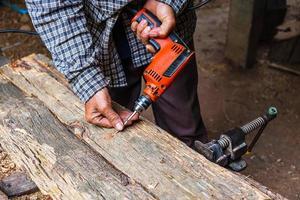 Mann mit Bohrmaschine auf Holzbrett in einer Holzbearbeitungswerkstatt