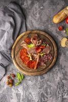 Salami-Anordnung auf einem runden Holzbrett foto