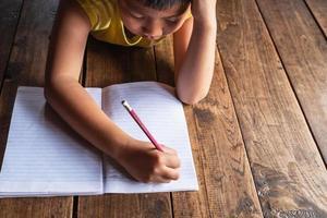 Junge, der auf Holzboden liegt und in Notizbuch schreibt foto