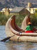peru 2015 - frau rudert ein schilfboot auf uros insel in peru