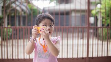 kleines Mädchen mit Spielzeugkamera foto