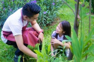 Vater unterrichtet Tochter im Garten foto