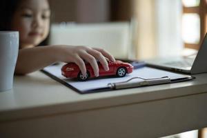 Mädchen spielt mit einem Spielzeugauto foto