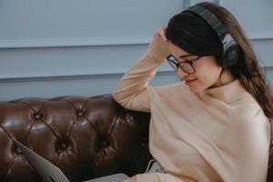 Frau, die Kopfhörer auf einem Laptop trägt foto