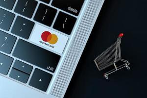 2018-- illustrativer Leitartikel des Mastercard-Symbols über Computertastatur mit Miniatur-Einkaufswagen foto