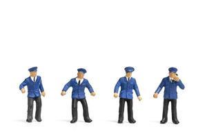 Miniaturpolizisten, die auf einem weißen Hintergrund stehen