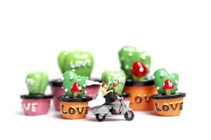 Miniaturpaar auf einem Motorrad neben Miniatur-Sukkulenten, Valentinstagskonzept