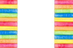 Reihen regenbogenfarbener Kreide lokalisiert auf einem weißen Hintergrund foto