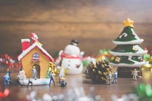 Miniaturmenschen, die Weihnachtsdekorationen auf einem hölzernen Hintergrund schaffen foto