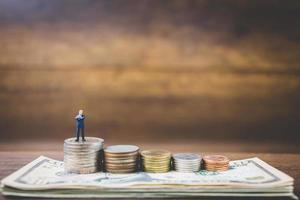 Miniaturgeschäftsleute auf Geld auf einem hölzernen Hintergrund