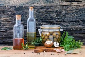 Speiseöle und frisches Gemüse und Kräuter foto