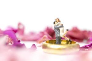 Miniaturpaar, das mit einem Ehering und rosa Blütenblättern umarmt lokalisiert auf einem weißen Hintergrund umarmt foto