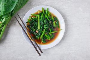 Gebratener chinesischer Grünkohl mit Austernsauce mit Stäbchen auf einem weißen Teller neben frischem chinesischem Grünkohl auf Holztisch foto