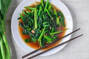 Gebratener chinesischer Grünkohl mit Austernsauce mit Stäbchen neben frischem chinesischem Grünkohl auf einem weißen Teller auf Holztisch foto