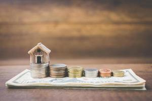Geld- und Hausmodell auf einem hölzernen Hintergrund-, Finanz- und Bankkonzept