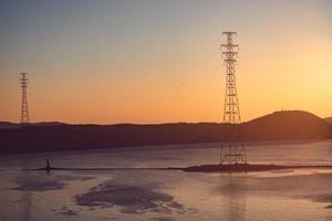 Seelandschaft mit Sonnenuntergang über dem Tokarev-Leuchtturm und der Amur-Bucht in Wladiwostok, Russland