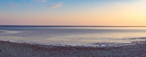 Panorama Seelandschaft des Strandes und des bunten bewölkten Himmels foto