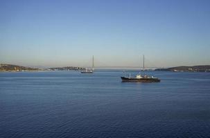 Seelandschaft mit Schiffen im Wasser und der russischen Brücke gegen einen klaren blauen Himmel in Wladiwostok, Russland