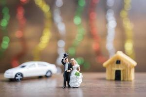 Miniatur Braut und Bräutigam auf einem Holzboden mit buntem Bokehhintergrund, erfolgreiches Familienkonzept foto
