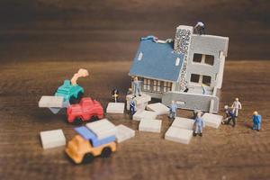 Miniaturarbeiter, die ein Haus auf einem hölzernen Hintergrund reparieren