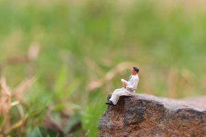 Miniaturgeschäftsmann, der eine Zeitung auf einem Felsen mit einem Naturhintergrund liest foto