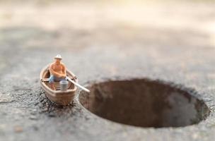 Miniaturfischer, der auf einem Boot fischt foto