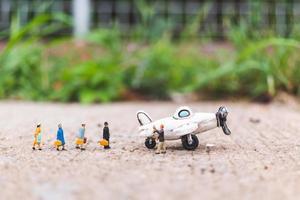 Miniaturreisende mit Handgepäck steigen in ein Flugzeug und erkunden das Weltkonzept foto