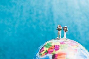Miniaturreisende mit Rucksäcken, die auf einer Weltkugel stehen und zu einem Ziel gehen foto