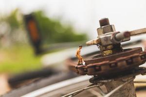 Miniaturmechaniker, die ein Fahrrad reparieren, Werkstattkonzept foto
