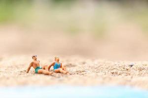 Miniaturmenschen, die Badeanzüge tragen, die auf einem Strand entspannen, Sommerkonzept foto