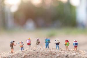 Miniaturreisende mit Rucksäcken auf Sand, Reise- und Abenteuerkonzept foto