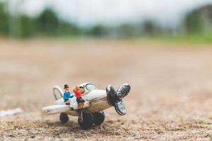 Miniaturpaar, das in einem Flugzeug sitzt und das Weltkonzept erforscht foto