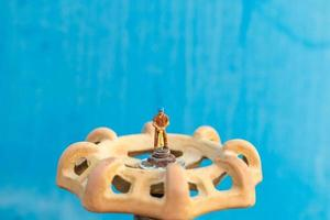 Miniaturinstallateur, der Wasserleitungen installiert und Schäden an einer Wasserpumpenmaschine überprüft foto