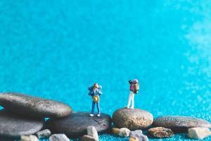Miniatur-Rucksacktouristen, Touristen auf einem blauen Glitzerhintergrund foto