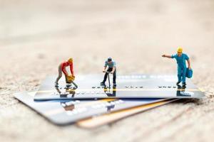 Miniaturarbeiter, die an einem Kreditkarten-, Geschäfts- und Finanzkonzept arbeiten