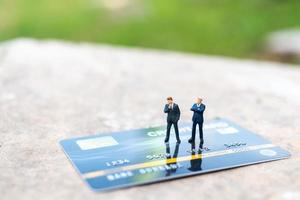 Miniatur-Geschäftsleute, die auf einer Kreditkarte, Geschäfts- und Finanzkonzepten stehen