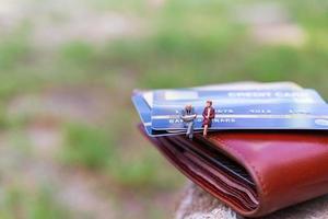 Miniatur-Geschäftsleute, die auf einer Kreditkarte sitzen, Geschäfts- und Finanzkonzepte