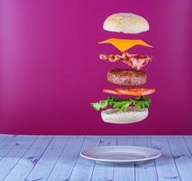 schwimmender Hamburger mit Speck und Käse foto