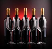 Weinflaschen und Gläser mit schwarzem und rotem Hintergrund foto