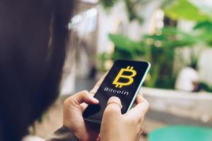 Frau nutzt mobiles Smartphone, um online mit Bitcoin Geld zu verdienen foto