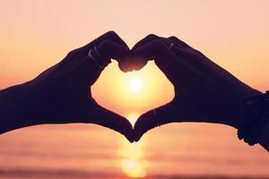 Frauenhand, die eine Herzform auf Sonnenuntergangshimmel und Bokehhintergrund macht foto