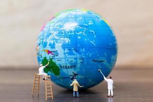 Miniaturmaler, die auf einem Globus mit einem hölzernen Hintergrund malen, retten das Erdkonzept foto