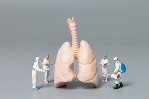 Miniaturärzte und Krankenschwestern, die das Konzept der menschlichen Lunge, des Virus und der mit Bakterien infizierten Menschen beobachten und diskutieren foto