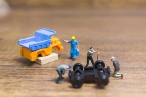 Miniaturarbeiter, die ein Rad von einem LKW auf einem hölzernen Hintergrund reparieren foto