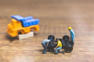 Miniaturarbeiter, die ein Rad von einem LKW auf einem hölzernen Hintergrund reparieren